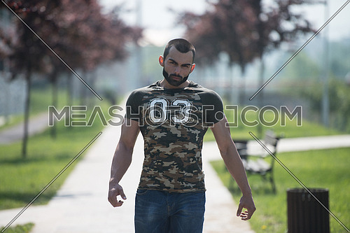 Young Man In A Shirt Stands In The Park And Relaxing