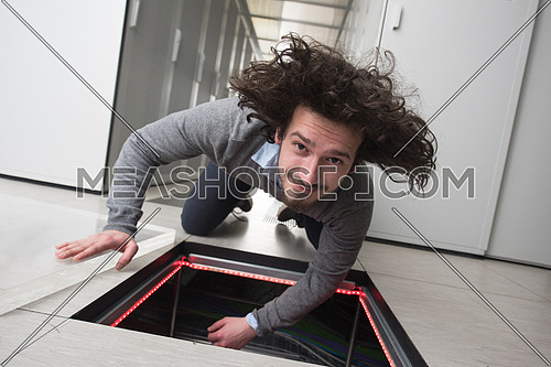 young IT engineer connecting cables in server room at modern data center