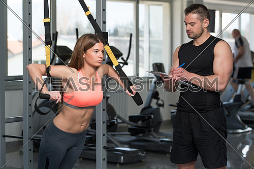 Personal Trainer Working With A Young Woman At The Gym Writing Notes On A Clipboard In A Health And Fitness Concept