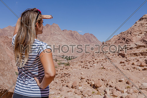 A female tourist from behind exploring Sinai Mountain for wadi freij by day.