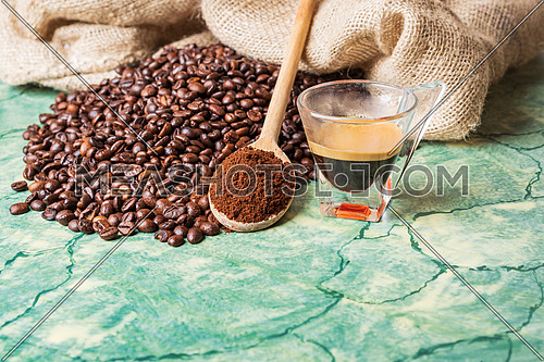 Coffee beans in coffee burlap bag on green surface,wooden spoon with ground coffee on top and coffee glass cup.