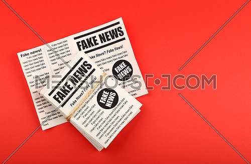 Close up stack of FAKE NEWS newspapers over red paper background with copy space, elevated top view, directly above