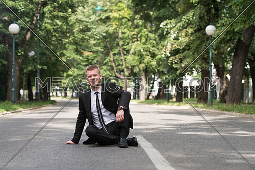 Happy Businessman Sitting on Asphalt Outdoors In Park