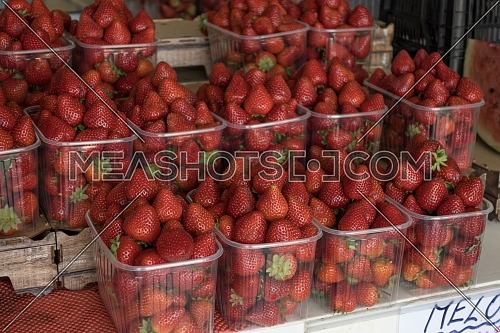 basket of red ripe strawberries for sale in the steet shop.