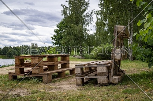 Rustic wooden table and benches made with pallets on the shore of a tranquil a lake surrounded by trees and greenery in summer sunshine