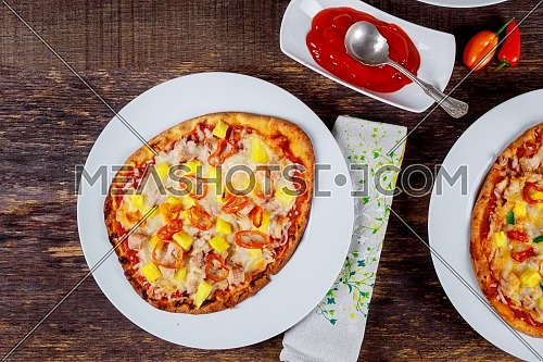shot from above delicious italian pizzas served on wooden table with ingredients