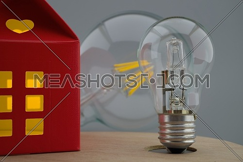 Incandescent lamp light bulbs next to a small red house of paper with a cut out heart and warm light in windows. Close-up concept of home lighting