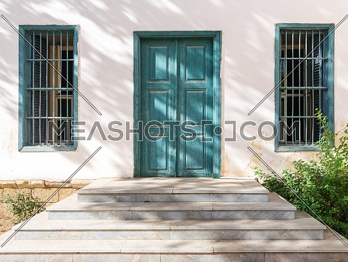 Marble stair in front of white wall with green wooden old grunge door and two wrought iron windows