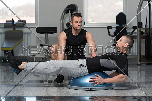 Personal Trainer Showing Young Man How To Train On Bosu Abs Exercise In A Health And Fitness Concept