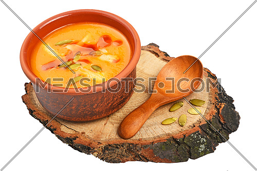 Small ceramic bowl of pumpkin cream soup, wooden spoon, slice of bread and seeds on wood cut isolated on white background, high angle view