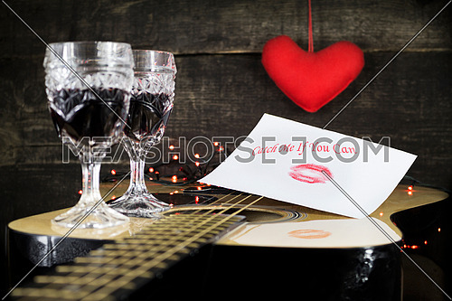 Happy Valentine's Day Kiss On White Paper With Text On it, Resting on Acoustic Guitar With Vine Glasses, Lights and Heart