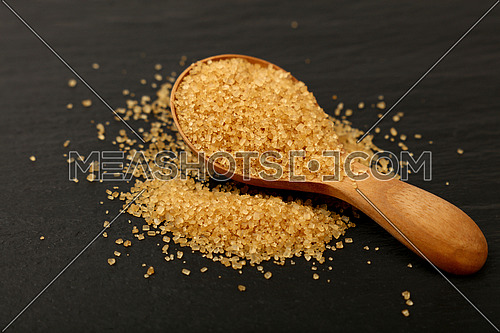 Close up one wooden scoop spoon full of brown cane sugar on black slate board, low angle view