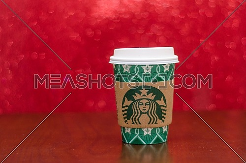 Starbucks takeaway paper cup, in special design for Christmas on a festive red background; December 2018 - Cairo, Egypt.