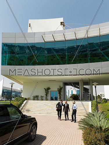 business people group walking as team in front of modern corporate middle eastern building