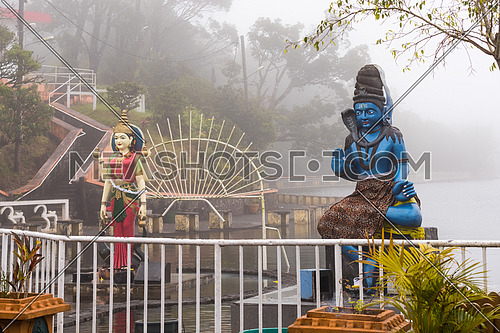 Statues of Shiva and Shakti in a hindu temple (Grand Basin), in the day with fog ,mystical atmosphere.Mauritius