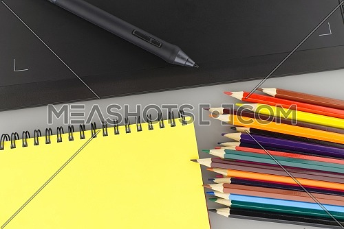 Digital stylus pen on digital graphic tablet for illustrators and designers opposite colored drawing pencils next to a wired notebook . Top view, free space for text