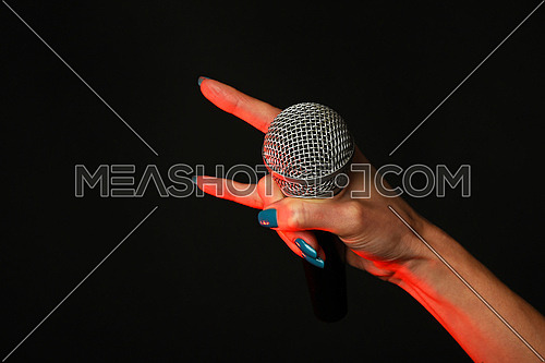 Woman hand with microphone with devil horns rock metal sign highlighted with red gun projector isolated on black background