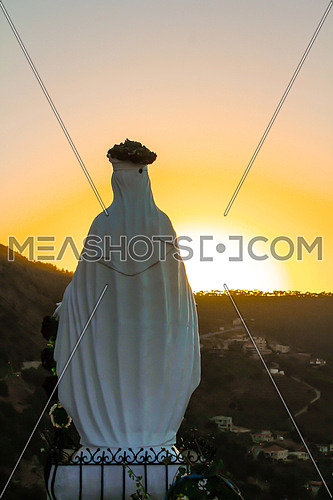 Sunset shot showing the back of a virgin Mary statue