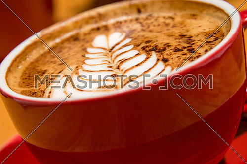 a red cup of cappuccino in a modern coffee shop