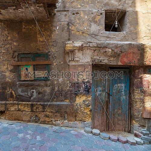 Grunge stone bricks wall with Broken wooden door and closed broken shutter window in abandoned Darb El Labana district, Cairo, Egypt