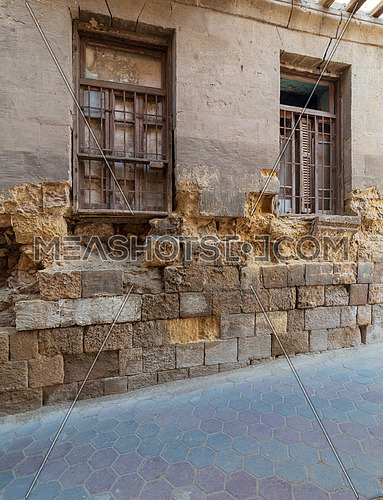Angled view of two adjacent broken windows and grunge stone bricks wall in abandoned Darb El Labana district, Cairo, Egypt