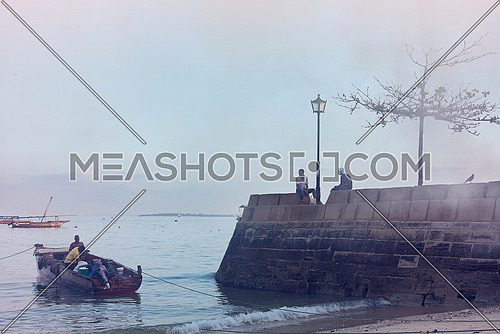 a small boat sailing in Stone Town at  Dawn