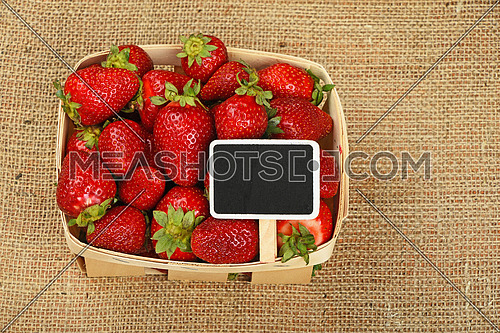 Wicker wooden basket full of red strawberries with chalk blackboard price tag sign on jute burlap canvas background, high angle view
