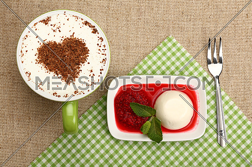 Close up serving panna cotta traditional Italian dessert with raspberry jam and cup of cappuccino coffee, elevated top view, directly above
