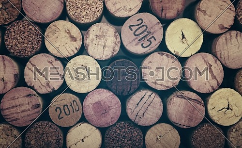 Close up background pattern of many assorted stacked used red wine corks, retro toned