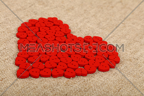Red heart shaped handmade wooden sewing buttons on linen canvas, low angle view, close up
