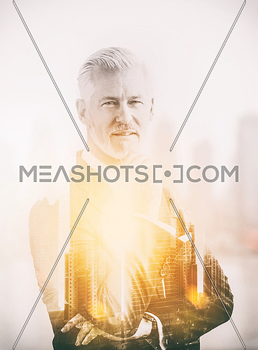 Double exposure of senior businessman in front of the big city