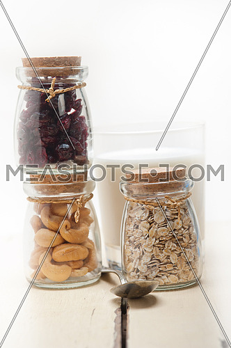 healthy breakfast ingredients milk oat cashew nuts dried cramberry craisinns