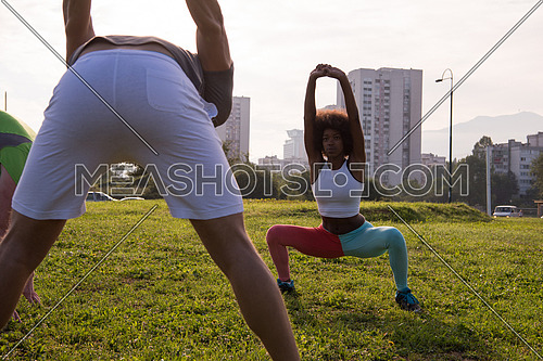 multiethnic group of young people stretching before running with the sunrise in the city