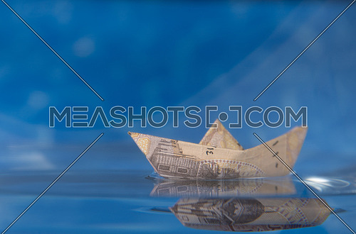one Egyptian Pound folded like paper boat floating in water concept