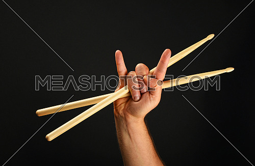 Man hand holding two crossed wooden drumsticks with devil horns rock metal gesture sign over black background, front view