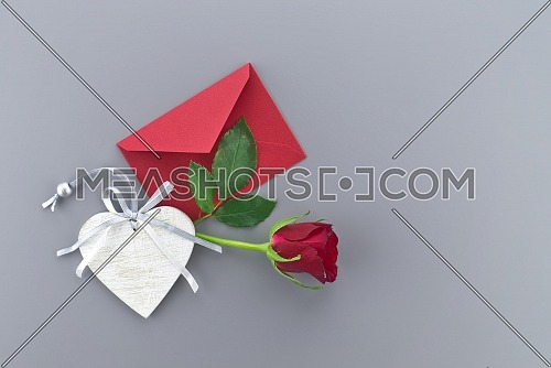Red rose and wooden heart medallion above the envelope on gray background with free copy space. Wishes, greetings and love message