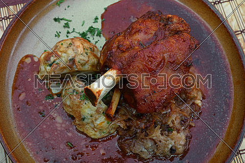 Big portion of roasted succulent pork fore shank or knuckle with Tyrolean dumplings and sauerkraut cabbage in plate on table, close up, elevated top view, directly above