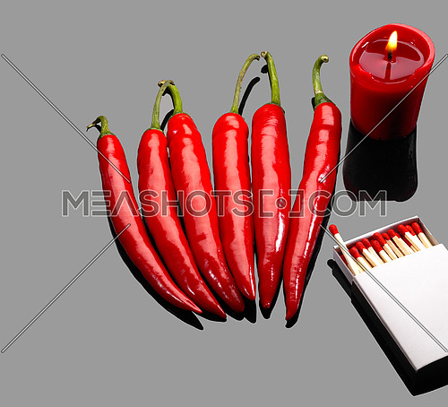 fresh red chili peppers  with matches and lighted red candle over grey reflective surface