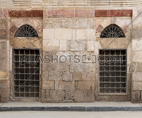 Old abandoned wall with two closed wooden windows covered by broken iron grid, El-Dard El-Ahmar, Cairo, Egypt