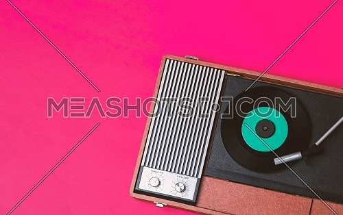Retro vinyl player and turnable on a fuchsia background. Entertainment 70s. Listen to music. Top view.