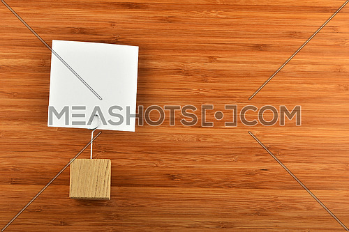 One single white paper note with wooden holder on bamboo wooden background for presentation