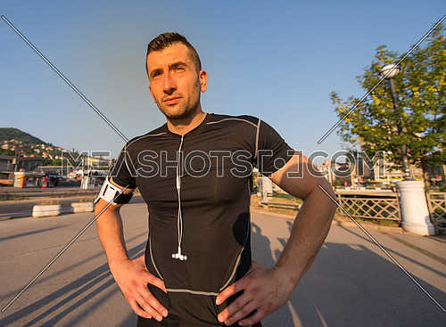 portrait of a young sporty jogging man at sunny morning in the city