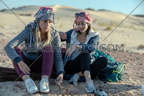 mid shot for two female tourists wearing bedouin traditions headscarf at Ain hodouda in Sinai by day