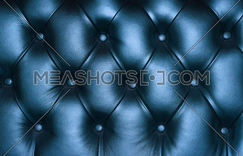 Dark blue capitone genuine leather background, retro Chesterfield style soft tufted furniture upholstery with deep diamond pattern and buttons, close up