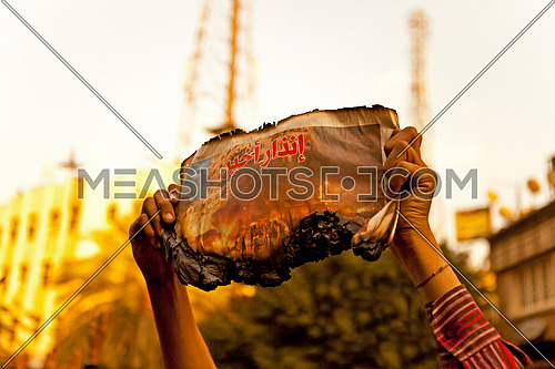 Man holding a burnt newspaper with title