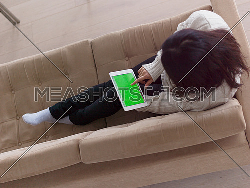 top view of young happy asian woman sitting on sofa using Digital Tablet