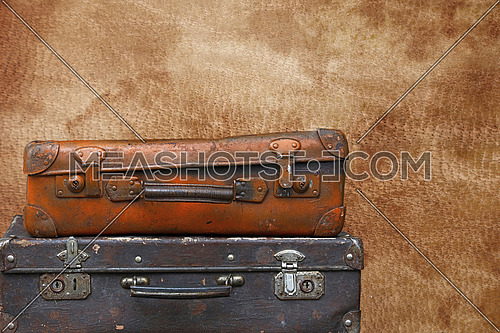 Close up stack of two old vintage antique grunge travel luggage brown leather suitcase trunks isolated over background of brown leather, low angle side view