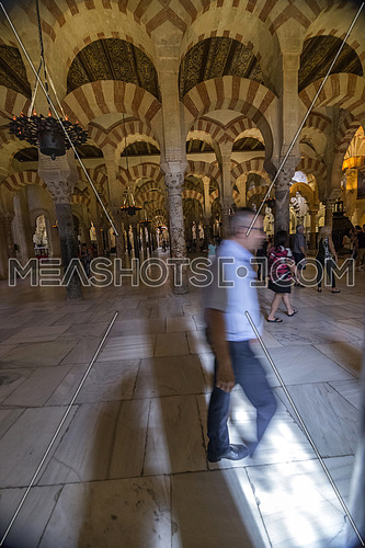 CORDOBA, SPAIN - September, 27, 2015: Interior of Mosque Cathedral, tourists walking inside the mosque, a medieval Islamic mosque that was converted into a Catholic Christian cathedral, UNESCO World Heritage Site, Cordoba, Spain