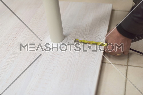 carpenter worker measuring distance for drilling holes in new furniture