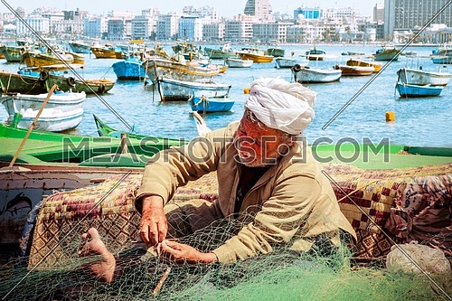 Elderly fisherman making fishnet